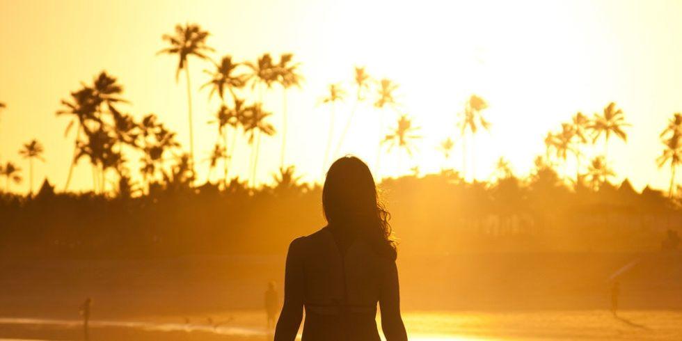 landscape-1477561984-woman-walking-sunset